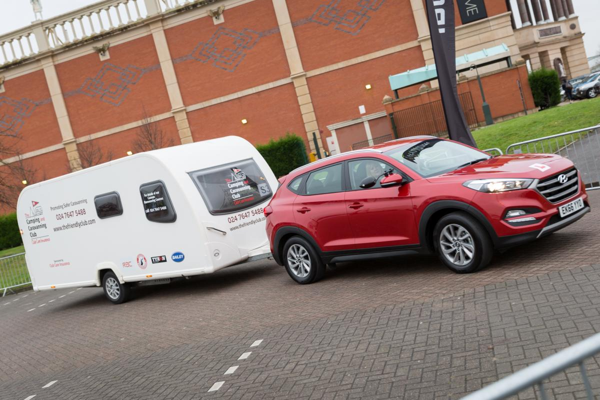 Red Hyundai towing a caravan